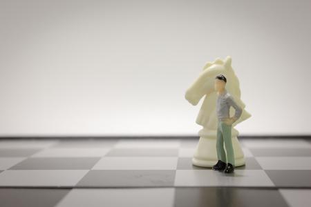 closeup miniature businessman in white chess knight on chess board. Foto de archivo