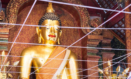 smiling golden buddha statue in Thai temple photo