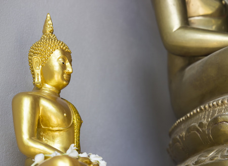 small golden buddha statue beside big buddha photo