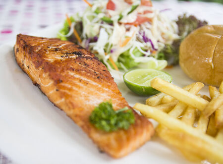 grilled salmon steak with bun, salad and french fried photo