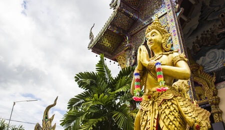asian angel: gold asian angel statue paying respect to buddha in front of temple