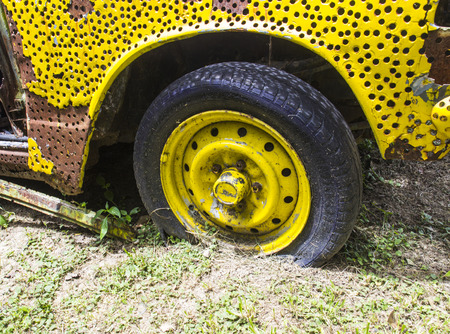 flatten: the flatten tyre of yellow rusty old car