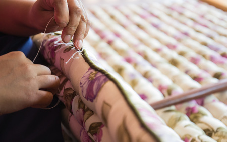 the view of seamstresss hand doing needlework to make the handmade mattress