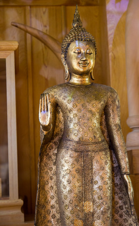 forbidding: ancient golden standing buddha statue with the forbidding hand acting