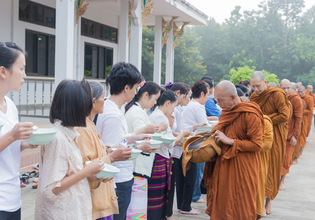 virtue: CHIANGMAI - OCTOBER 12: People put food offerings in a Buddhist monks alms bowl for virtue at Palun temple in Fang district in Chiangmai, Thailand on October 12, 2014. Editorial