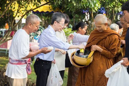 virtue: CHIANGMAI - OCTOBER 19: People put food offerings in a Buddhist monks alms bowl for virtue at Suantummarot temple in Doilor district in Chiangmai, Thailand on October 19, 2014.