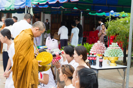 virtue: Khonkaen, Thailand - October 26, 2014: People put food offerings in a Buddhist monks alms bowl for virtue at Wiweksikkaram Forest Monastery in Pon district. Editorial