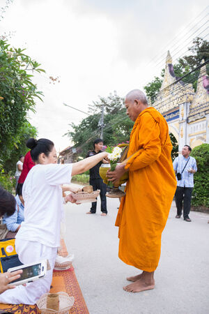 Loei, Thailand - October 27, 2014: People put food offerings in a Buddhist monks alms bowl for good merit at Chiangkarn district. Editorial