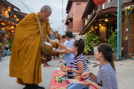 Loei, Thailand - October 27, 2014: People put food offerings in a Buddhist monk's alms bowl for good merit at Chiangkarn district.