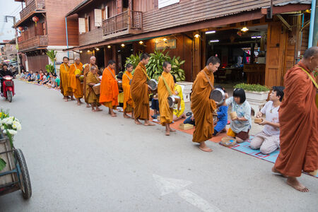 limosna: Loei, Tailandia - 27 de octubre 2014: La gente puso ofrendas de comida en la limosna de un monje budista tazón de buen mérito al distrito Chiangkarn.