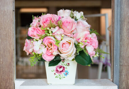 flower bunch: fake pink rose bouquet in white vase decorating on wooden frame Stock Photo