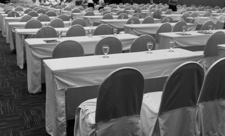 empty table and chair with fabric covering in convention hall