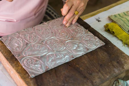 graver: Chiangmai, Thailand - November 4, 2014: The silversmith using the graver to engrave art tracery on silverware at Srisuphan temple in Muang district in Chiangmai province. Stock Photo