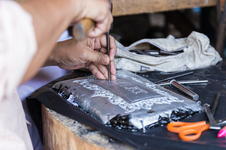 graver: Chiangmai, Thailand - November 4, 2014: The silversmith using the graver to engrave art tracery on silverware at Srisuphan temple in Muang district in Chiangmai province. Editorial