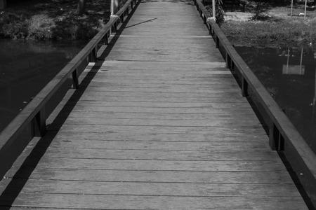 across: small wooden bridge across the lake in the garden