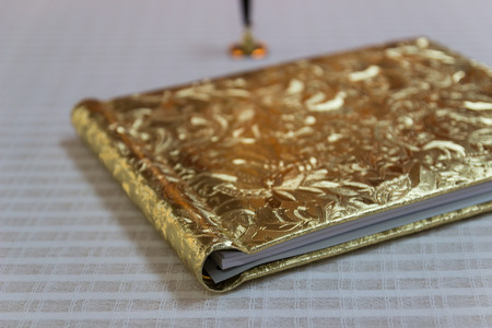 hardcovers: book with golden hardcover with flower tracery on white tablecloth