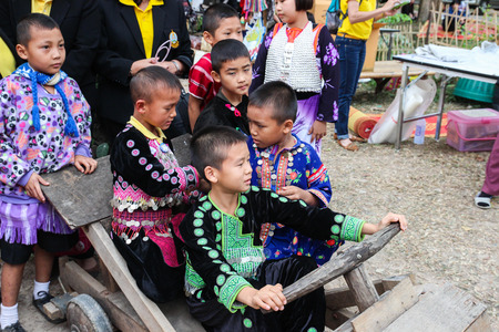 Chiangmai, Thailand - December 18, 2014: thailand hill tribe boy with traditional northern tribe costume on wooden car toy in royal project fair at Chiangmai university.