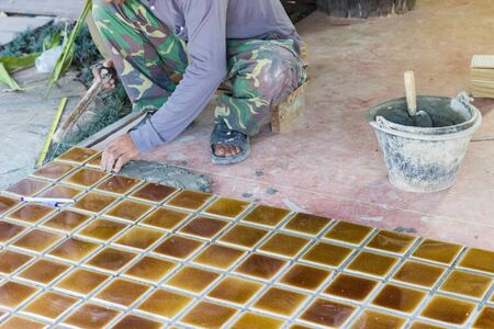 worker is laying brown ceramic tile on the floor photo