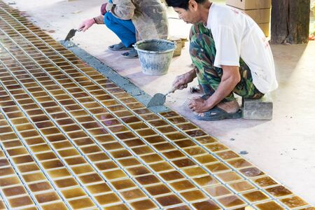 Uttaradit, Thailand - December 19, 2014: The worker is laying brown ceramic tile on the floor in Lomyen shop.