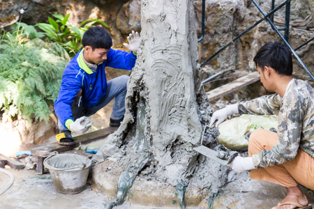 grout: Uttaradit, Thailand - December 19, 2014: The workers are grout cement on the fake tree trunk in Lomyen shop.