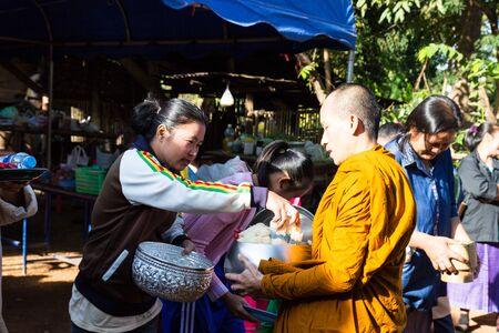limosna: Sakon Nakhon, Tailandia - 20 de diciembre 2014: La gente a llevar alimentos a monje budista cuenco de las limosnas en Sakon Nakhon, Tailandia el 20 de diciembre de 2014. Editorial