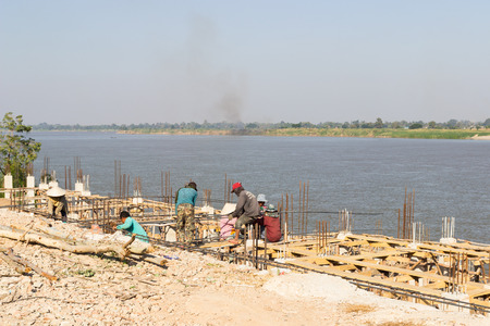 constructing: Nakhon Phanom, Thailand - December 20, 2014:  The workers are constructing the pier beside Mekong river in Nakhon Phanom, Thailand near the border between Thailand and Laos on December 20, 2014.