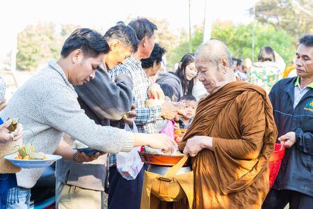 december 21: Sakon Nakhon, Thailand - December 21, 2014: People offer food on buddhist monk alms bowl in Sakon Nakhon, Thailand on December 21, 2014. Editorial