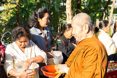 limosna: Sakon Nakhon, Tailandia - 21 de diciembre 2014: Las personas ofrecen comida en monje budista cuenco de las limosnas en Sakon Nakhon, Tailandia el 21 de diciembre de 2014.