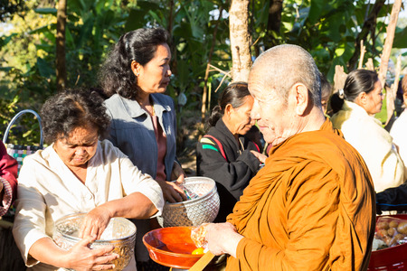 alms: Sakon Nakhon, Thailand - December 21, 2014: People offer food on buddhist monk alms bowl in Sakon Nakhon, Thailand on December 21, 2014. Editorial