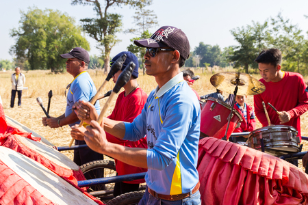 playing folk: Sakon Nakhon, Thailand - December 21, 2014:  Thailand traditional musician hillbilly band playing country folk music in rice paddy field in Sakon Nakhon, Thailand on December 21, 2014.