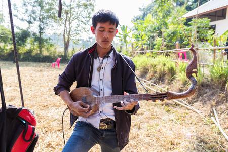 hillbilly: Sakon Nakhon, Thailand - December 21, 2014:  Thailand traditional musician hillbilly playing country folk music in rice paddy field in Sakon Nakhon, Thailand on December 21, 2014.