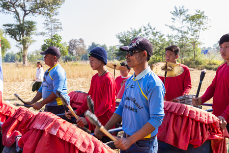 december 21: Sakon Nakhon, Thailand - December 21, 2014:  Thailand traditional musician hillbilly band playing country folk music in rice paddy field in Sakon Nakhon, Thailand on December 21, 2014.