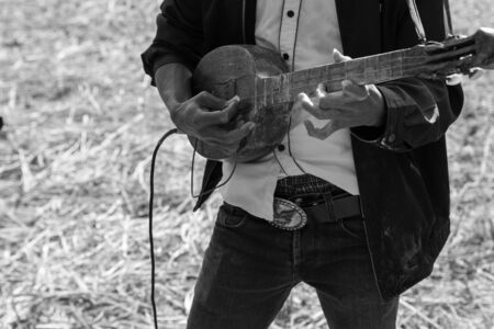 playing folk: Thailand traditional musician hillbilly playing country folk music in rice paddy field, black and white