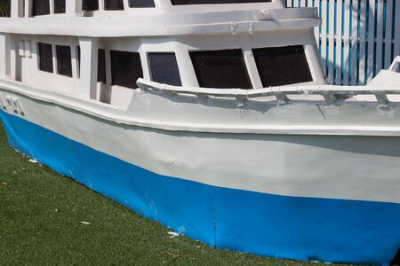 artificial model: old blue and white model ship on artificial grass