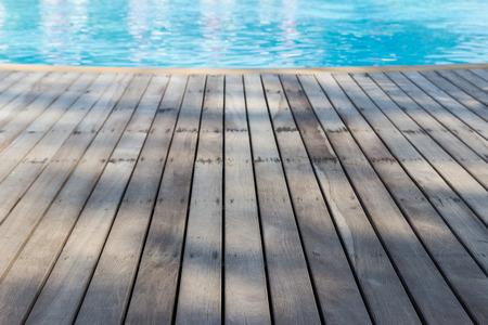 perspective view of wooden floor beside swimming pool