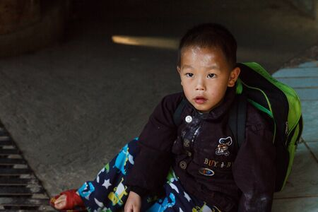 Chiangmai, Thailand - January 26, 2015: thailand hill tribe boy sitting on the street at Doi Pui which is the tourist attraction in Chiangmai.