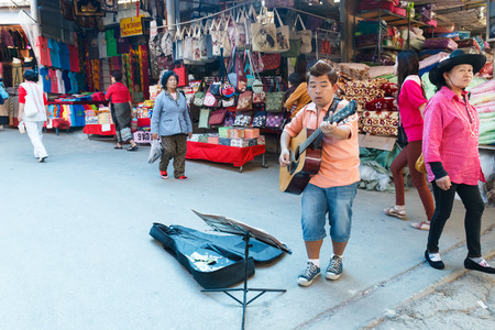 playing the market: Chiangrai, Thailand - February 8, 2015: Street musician playing guitar at Maesai market.