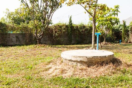 underground cement cylinder of lavatory cesspit in lawn yard Reklamní fotografie - 39121017