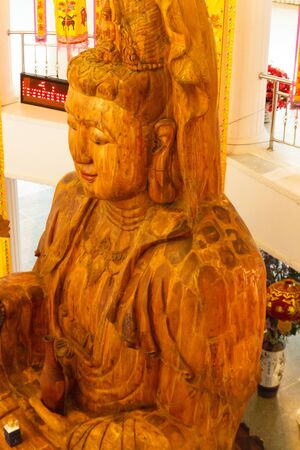 mercy: wooden goddess of mercy (Guan Yin) statue in asian temple Stock Photo