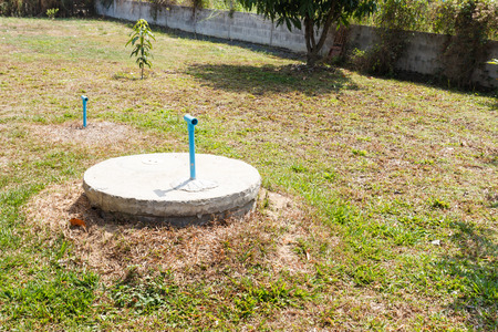 cesspool: underground cement cylinder of lavatory cesspit in lawn yard Stock Photo