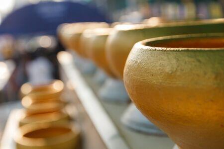 limosna: fila de oro budista monje cuenco de las limosnas que la gente done dinero en el templo Foto de archivo