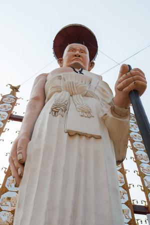 Robe: buddhist monk in white robe statue with walking stick