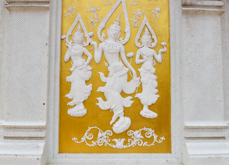asian angel: white angel sculpture on golden wall in asian temple