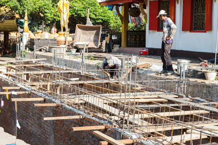 Chiang Mai, Thailand - April 26, 2015: The worker is constructing underground floor of the building in Rampoeng temple.
