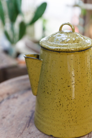 tiffin: old yellow jug and tiffin on wooden desk