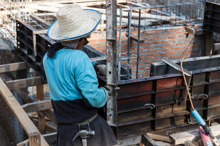 Chiang Mai, Thailand - April 26, 2015: The worker is constructing underground floor of the building in Rampoeng temple. photo