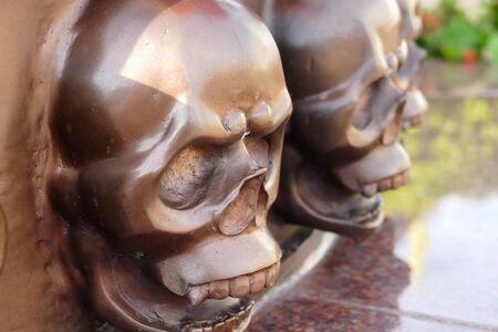 cranium: row of brown metal skull sculpture decorating in temple Stock Photo