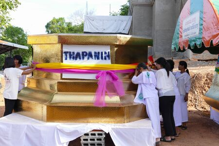 religious clothing: Khon Kaen, Thailand - June 1, 2015: People hold colorful cloth around the pagoda structure which is the buddhist culture  at Tumpadang Panimit temple on June 1, 2015 in Khon Kaen, Thailand.