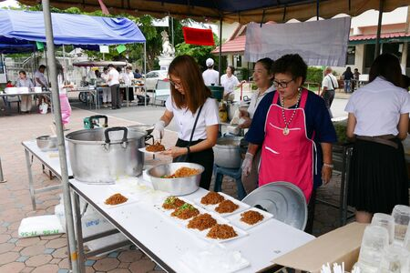 dhamma: Chiang Mai, Thailand -  July 26, 2015: The girl is preparing noodle for give for free for any people who participating in Dhamma talk fair arranged at Suandok temple. Editorial