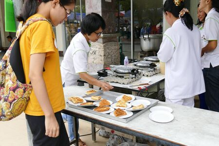 dhamma: Chiang Mai, Thailand -  July 26, 2015:The girl is getting waffle that give for free for any people who participating in Dhamma talk fair arranged at Suandok temple.